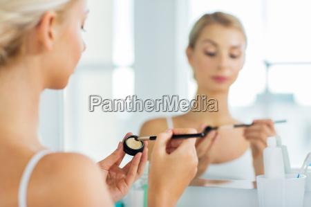 kvinde med makeup borste og eyeshade