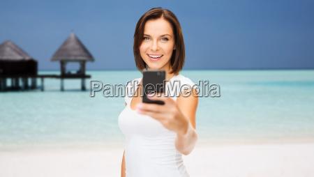glad kvinde tager billede af smartphone