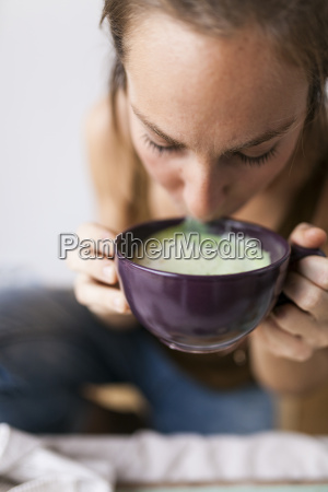 kvinde drikker matcha latte derhjemme