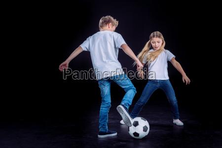 bror og soster leger med fodbold