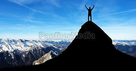 mand staende pa toppen af bjerget