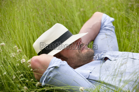 serene man wearing fedora sleeping in