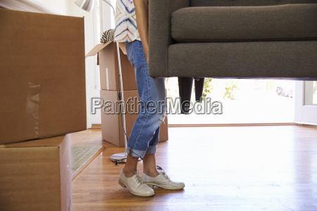 close up of woman carrying sofa