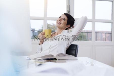 smilende kvinde holder kop kaffe pa