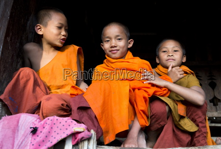 three novice monks in village near