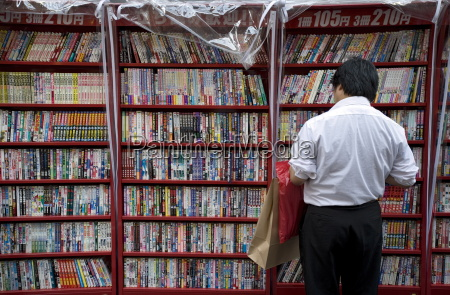 man browsing japanske manga tegneserier pa