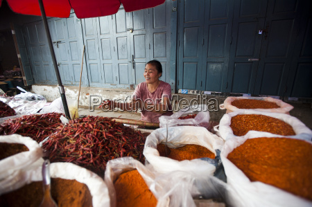 a woman selling spices on a
