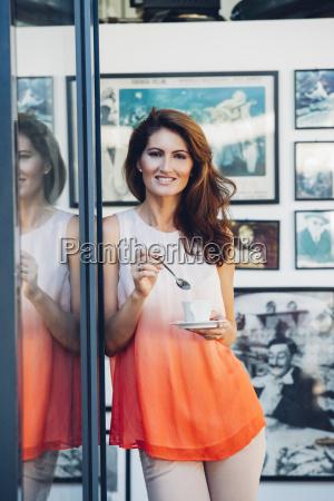 smilende kvinde udendors holder kop kaffe