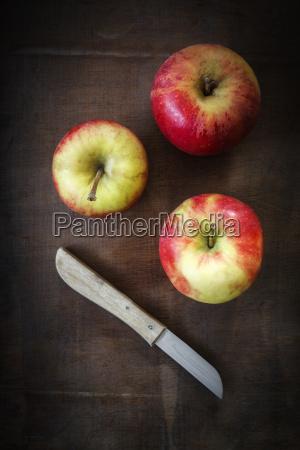 tre aebler og kokkenkniv pa morkt