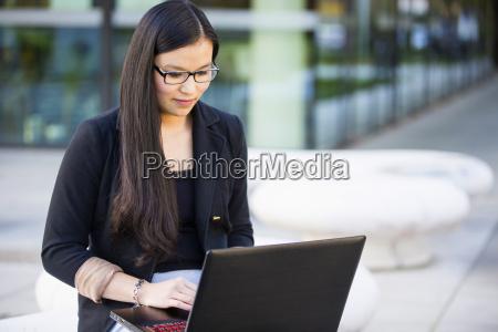 ung forretningskvinde ved hjaelp af baerbar