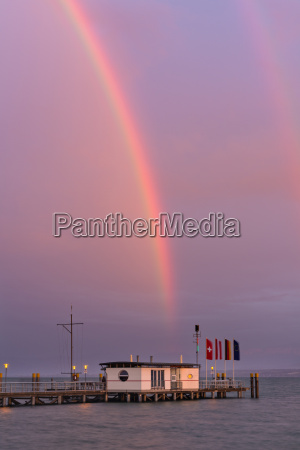 germany rainbow over ferry jetty with