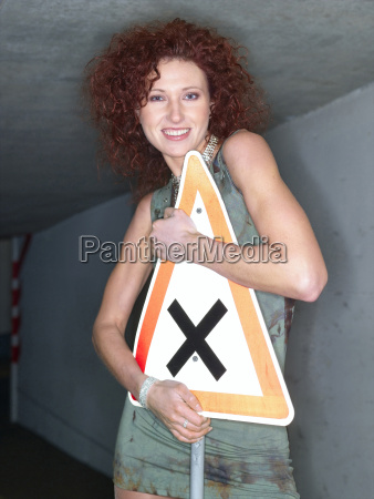 young woman holding traffic sign smiling
