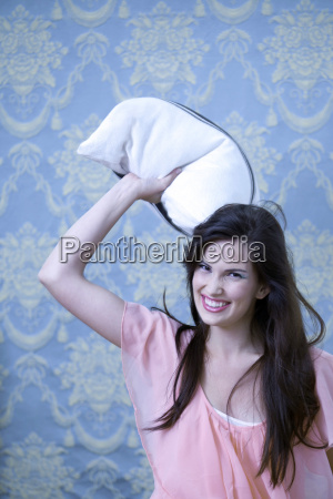 germany munich young woman throwing pillow