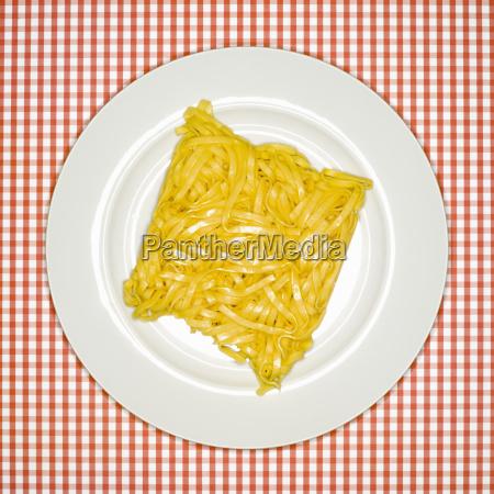 uncooked tagliatelle pasta on plate elevated