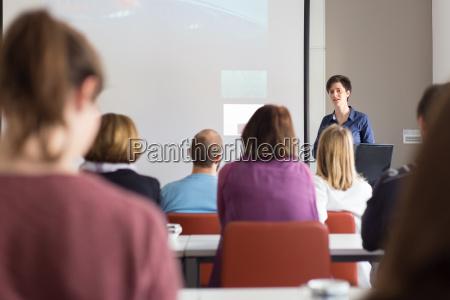 kvinde giver praesentation i auditoriet pa