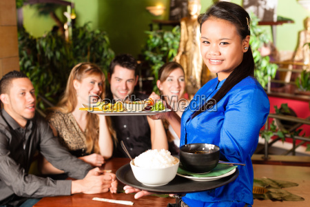 young people with waitress eating in