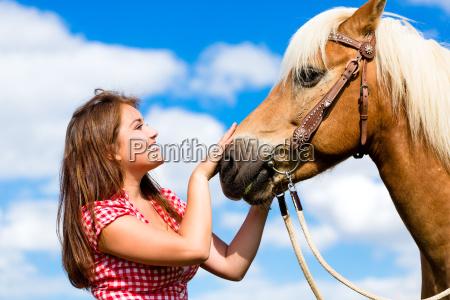woman petting horse on pony farm