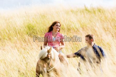 couple leading horse thru summer meadow