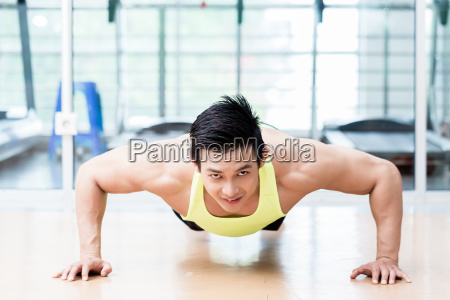 muskulos asiatisk mand gor pushups i