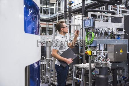 mand kigger pa skaermen i fabrikken