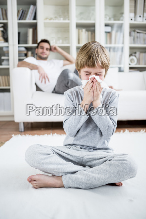 boy blowing his nose at home