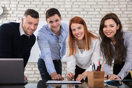 glade forretningsfolk der arbejder pa arbejdspladsen