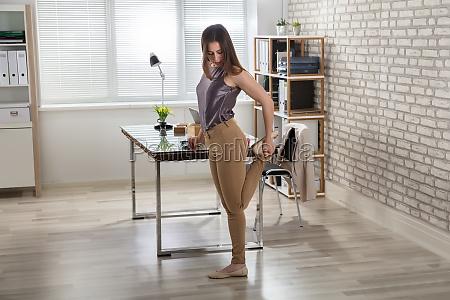 forretningskvinde straekker hendes ben i office