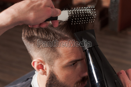 the hands of barber making haircut