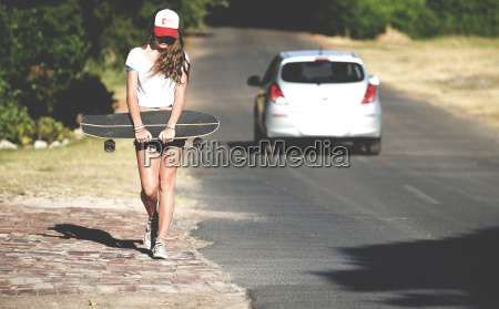 young woman walking beside a road