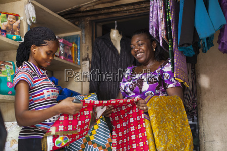 a female shopkeeper showing different colourful