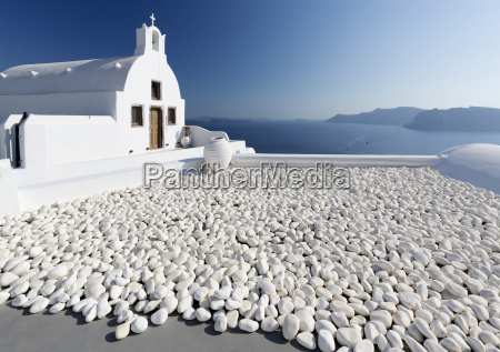 small whitewashed church against blue sea
