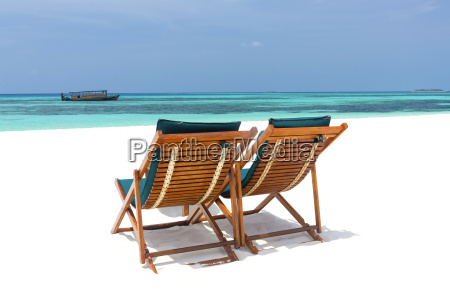 wooden sun loungers on beach coco