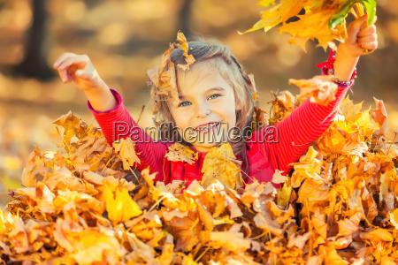 happy little girl leger med efterarsblade