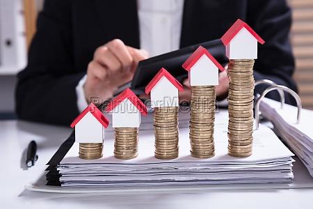 forretningskvinde beregne faktura med hus modeller