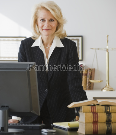 businesswoman leaning on desk
