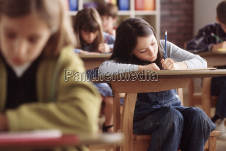 elementary school students writing at their