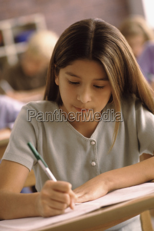 elementary school student writing at her