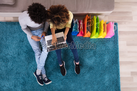 young couple shopping online on laptop