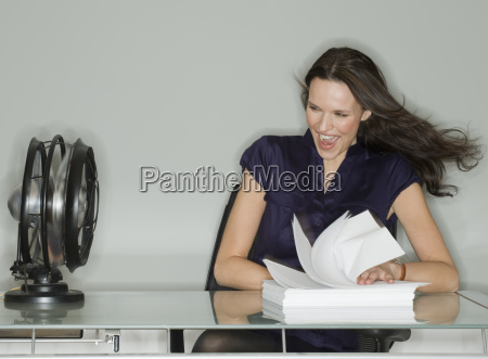 fan blowing stack of papers at