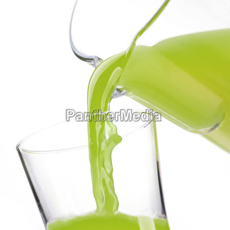 pouring detox green juice in a