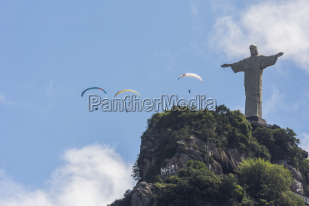 paragliders flying over famous christ the