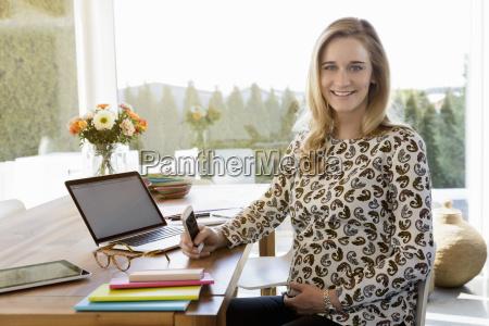 portraet af smilende gravid kvindeder arbejder
