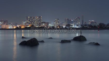 view of illuminated cityscape by sea