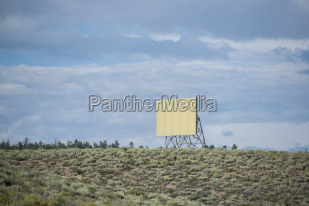 blank billboard on field against cloudy
