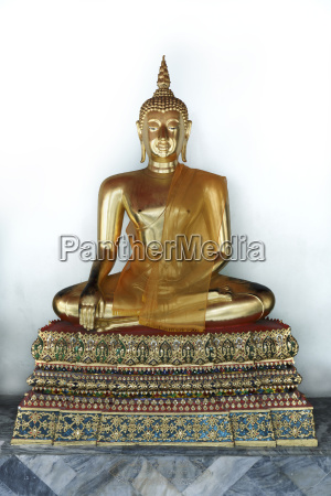 golden buddha statue against white wall
