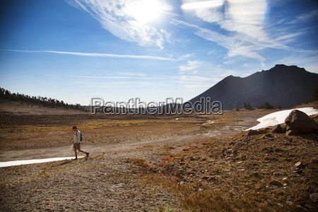 hiker walking on field against sky