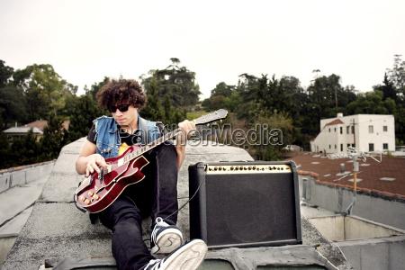 man playing electric guitar while sitting