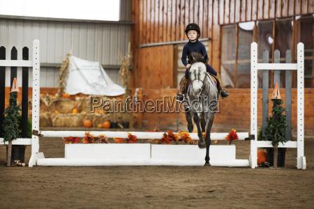boy riding horse at field