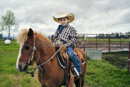 portrait of cute cowboy riding horse