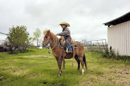 cute cowboy riding horse on ranch
